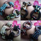 women stretching bracelet beads with wood tire